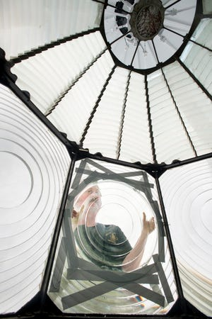 Kurt Fosburg, owner of Superior Lighthouse Restoration, moves a Fresnel lens into place Friday in the lantern room atop the Pensacola Lighthouse.