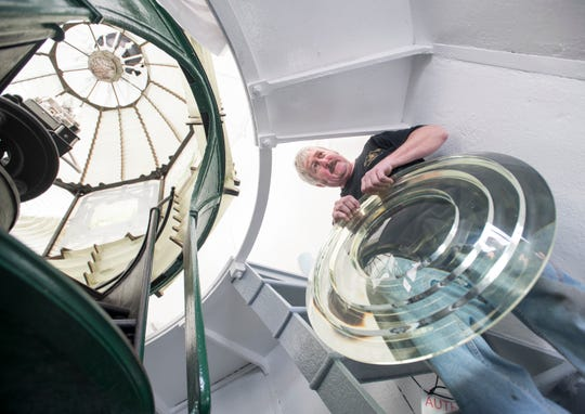 Kurt Fosburg with Superior Lighthouse Restoration carries a first-order Fresnel lens up a ladder at the Pensacola Lighthouse on Dec. 14.