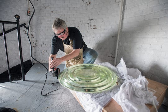 Kurt Fosburg, owner of Superior Lighthouse Restoration, grinds the edges of a Fresnel lens to fit into place Friday at the Pensacola Lighthouse.