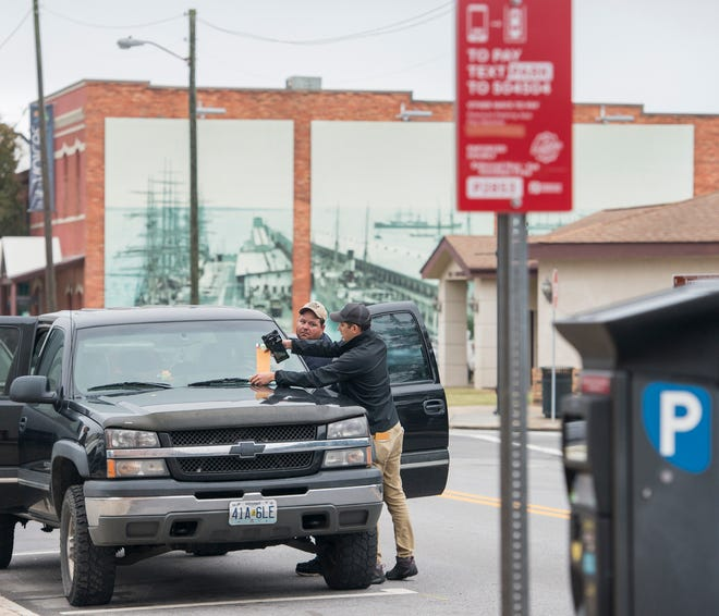 """At left, Gary Zappala, of Silex, Missouri, looks on as Pensacola Downtown Improvement Board """"parking ambassador"""" Mark Horn places a """"This Is Not A Parking Ticket"""" card on his vehicle Friday to announce Parking Amnesty Week."""