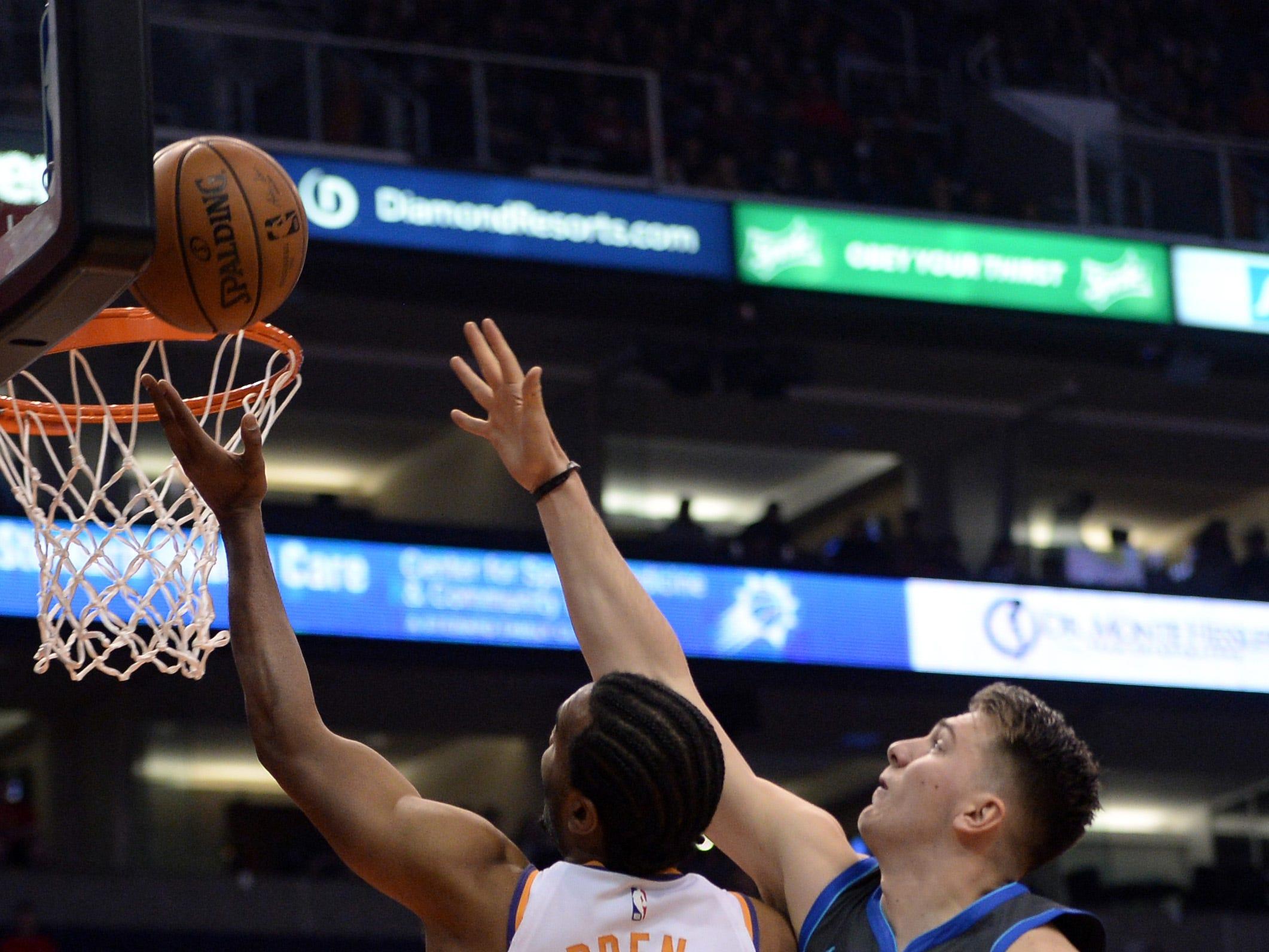 Dec 13, 2018; Phoenix, AZ, USA; Phoenix Suns forward T.J. Warren (12) puts up a layup over Dallas Mavericks forward Luka Doncic (77) during the first half at Talking Stick Resort Arena. Mandatory Credit: Joe Camporeale-USA TODAY Sports
