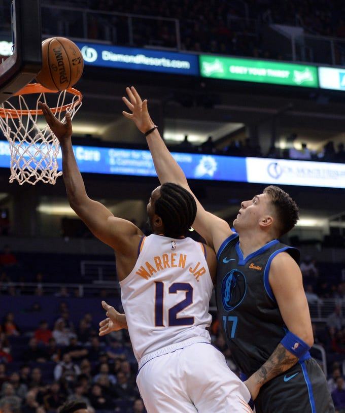 Dec 13, 2018; Phoenix, AZ, USA; Phoenix Suns forward T.J. Warren (12) puts up a layup over Dallas Mavericks forward Luka Doncic (77) during the first half at Talking Stick Resort Arena. Mandatory Credit: Joe Camporeale-USA TODAY Sports