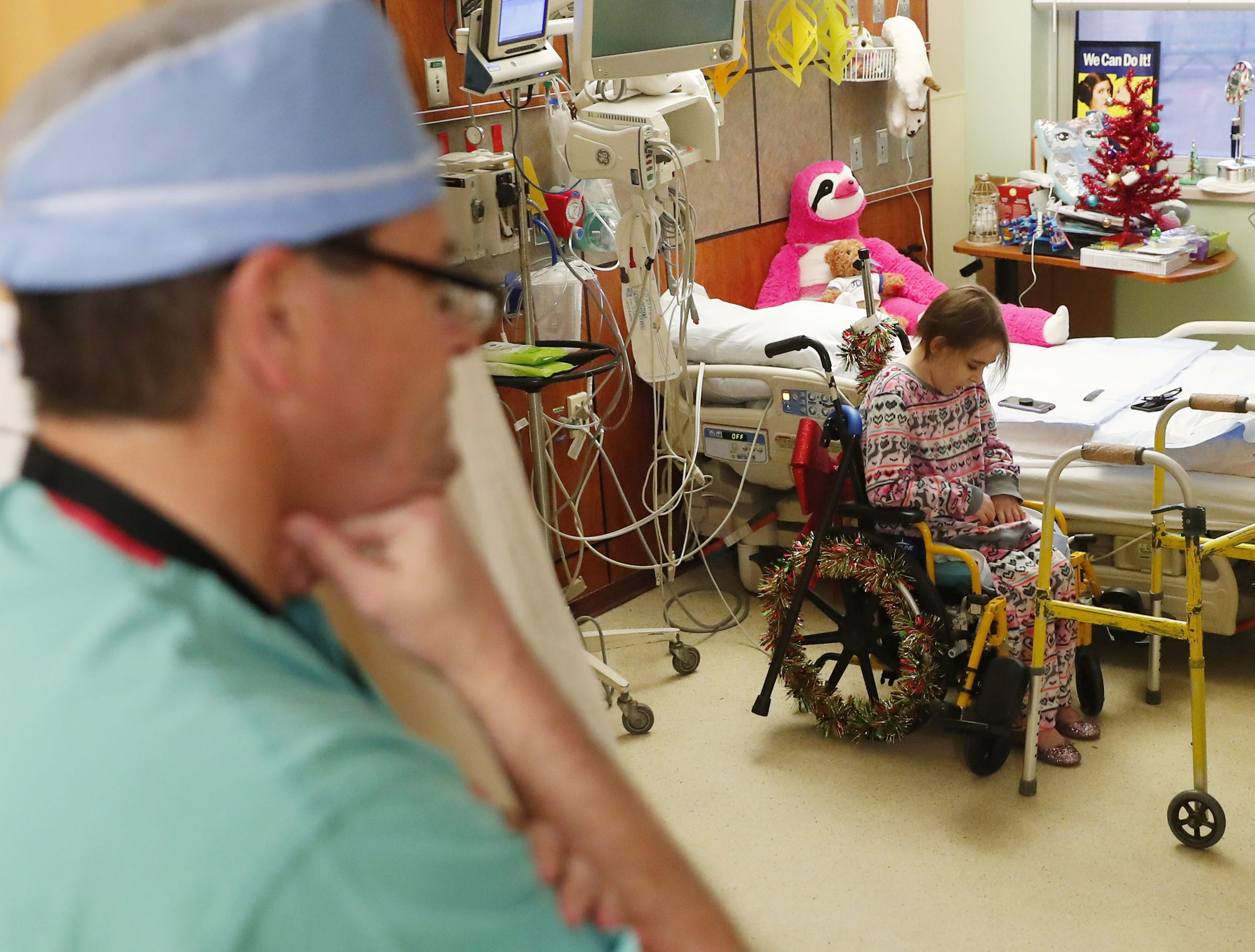 Dr. Kevin Foster talks with Isabella McCune in her room at the Arizona Burn Center in Phoenix Dec. 12, 2018. The 9-year-old was severely burned in a home accident in March.