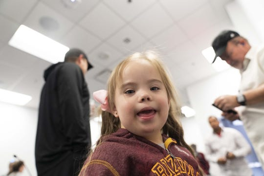Abby smiles for the camera while her dad, ASU defensive coordinator Danny Gonzales, gets ready for a news conference.