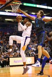 Phoenix Suns forward Richaun Holmes is pressured by Dallas Mavericks' Dirk Nowitzki during a game on Dec. 13 at Talking Stick Resort Arena.