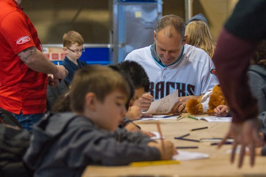 Torey Lovullo, the field manager for the Diamondbacks, draws with children during  the Arizona Diamondbacks annual Winter Classic Holiday Party inside Chase Field in Phoenix, Arizona on Friday, Dec. 14, 2018.