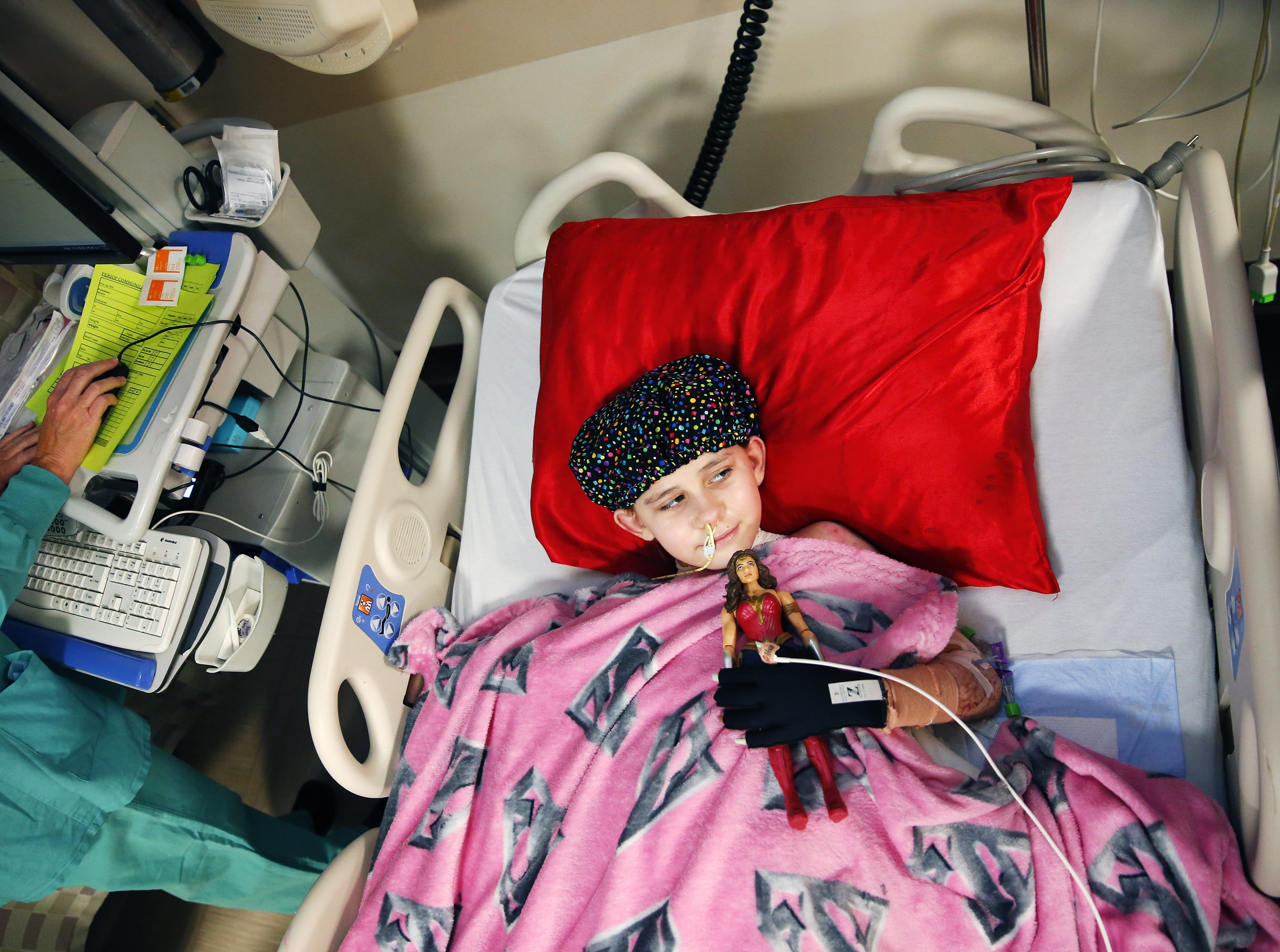 Isabella McCune holds a Wonder Woman doll before surgery at the Arizona Burn Center in Phoenix on May 24, 2018. She was severely burned in a home accident in March.