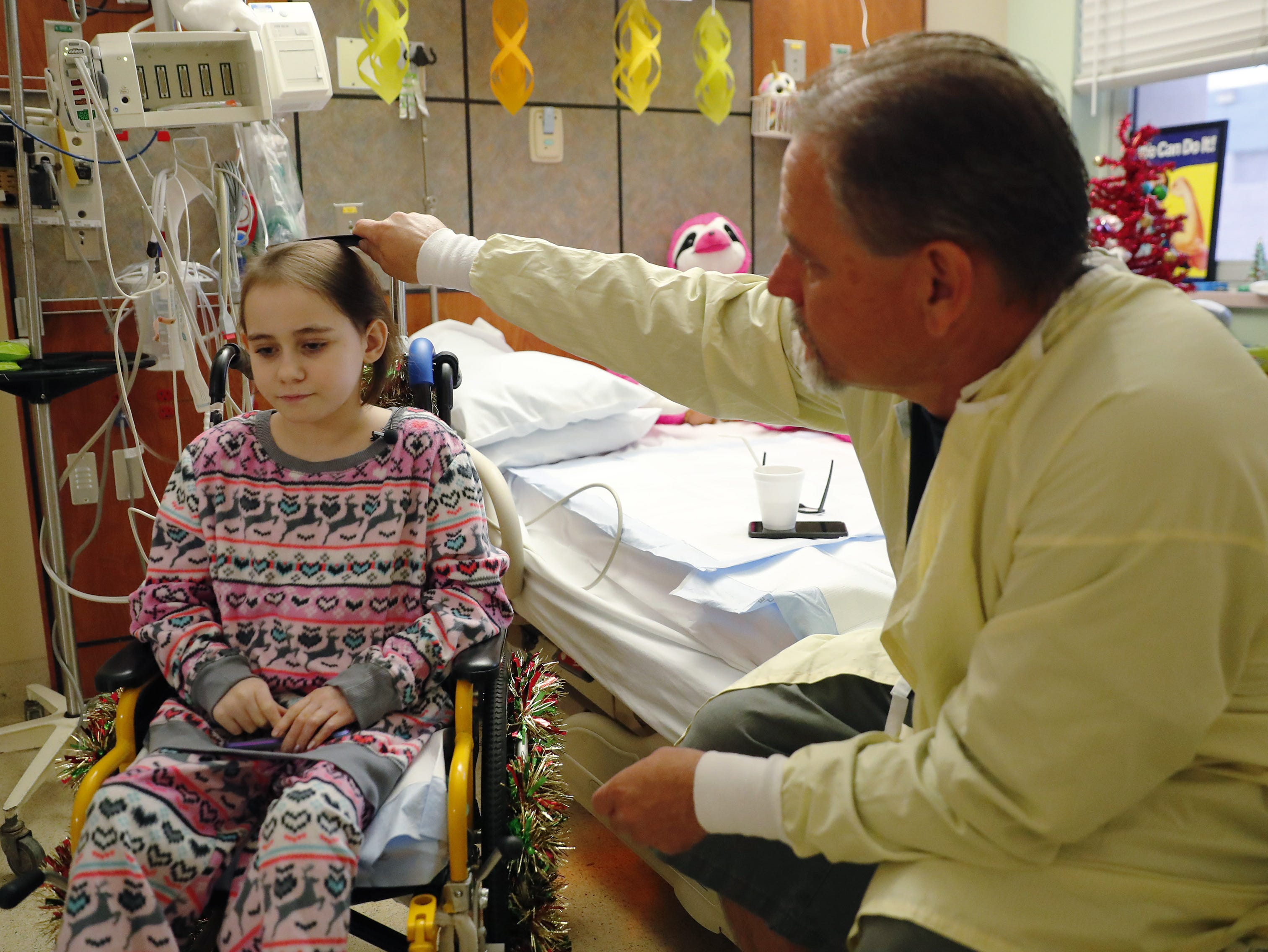Isabella McCune has her hair combed by her dad, J.D., in her room at the Arizona Burn Center in Phoenix Dec. 12, 2018. The 9-year-old was severely burned in a home accident in March.