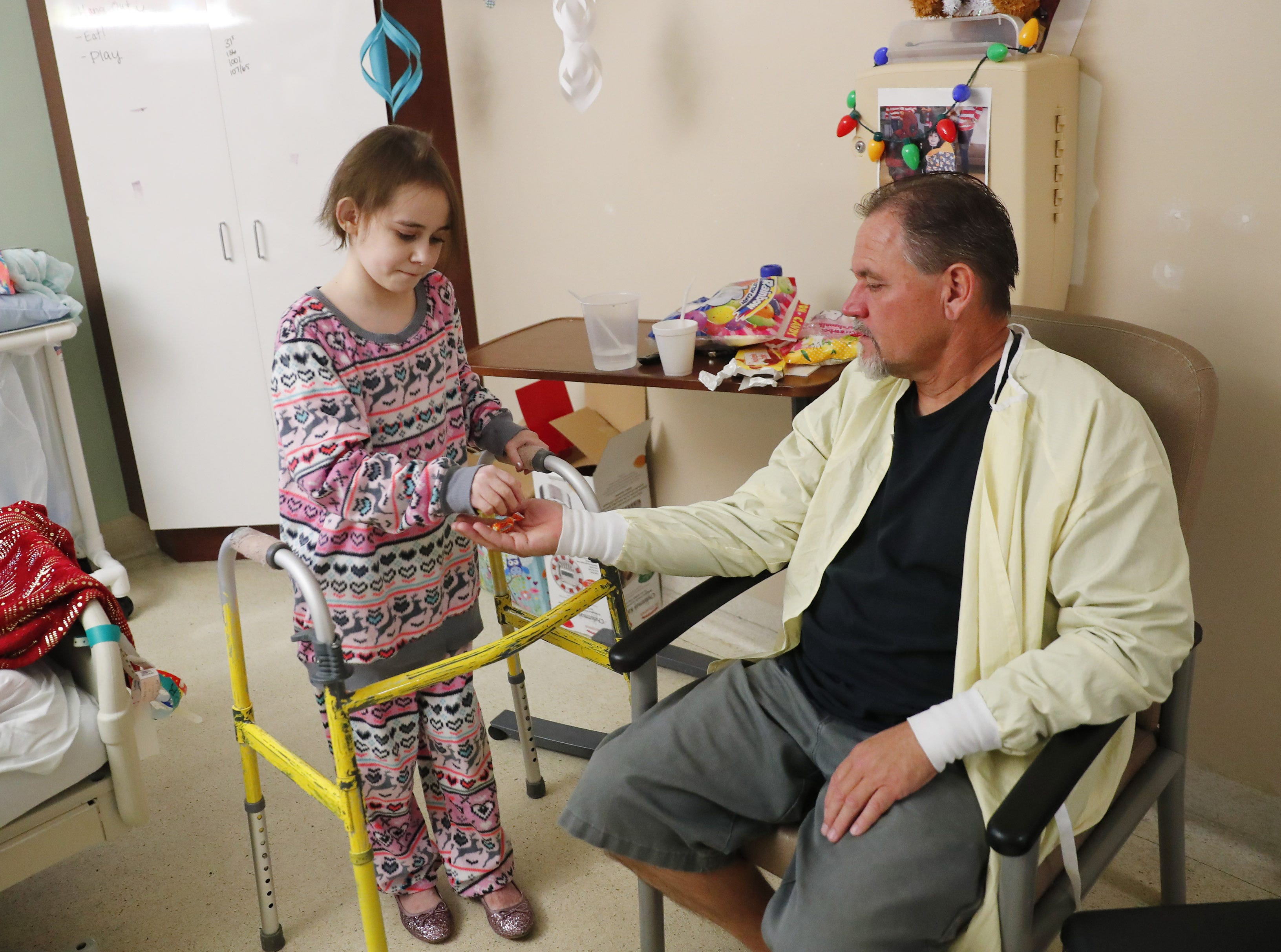 Isabella McCune gives candy to her dad, J.D., in her room at the Arizona Burn Center in Phoenix on Dec. 12, 2018. The 9-year-old was severely burned in a home accident in March.