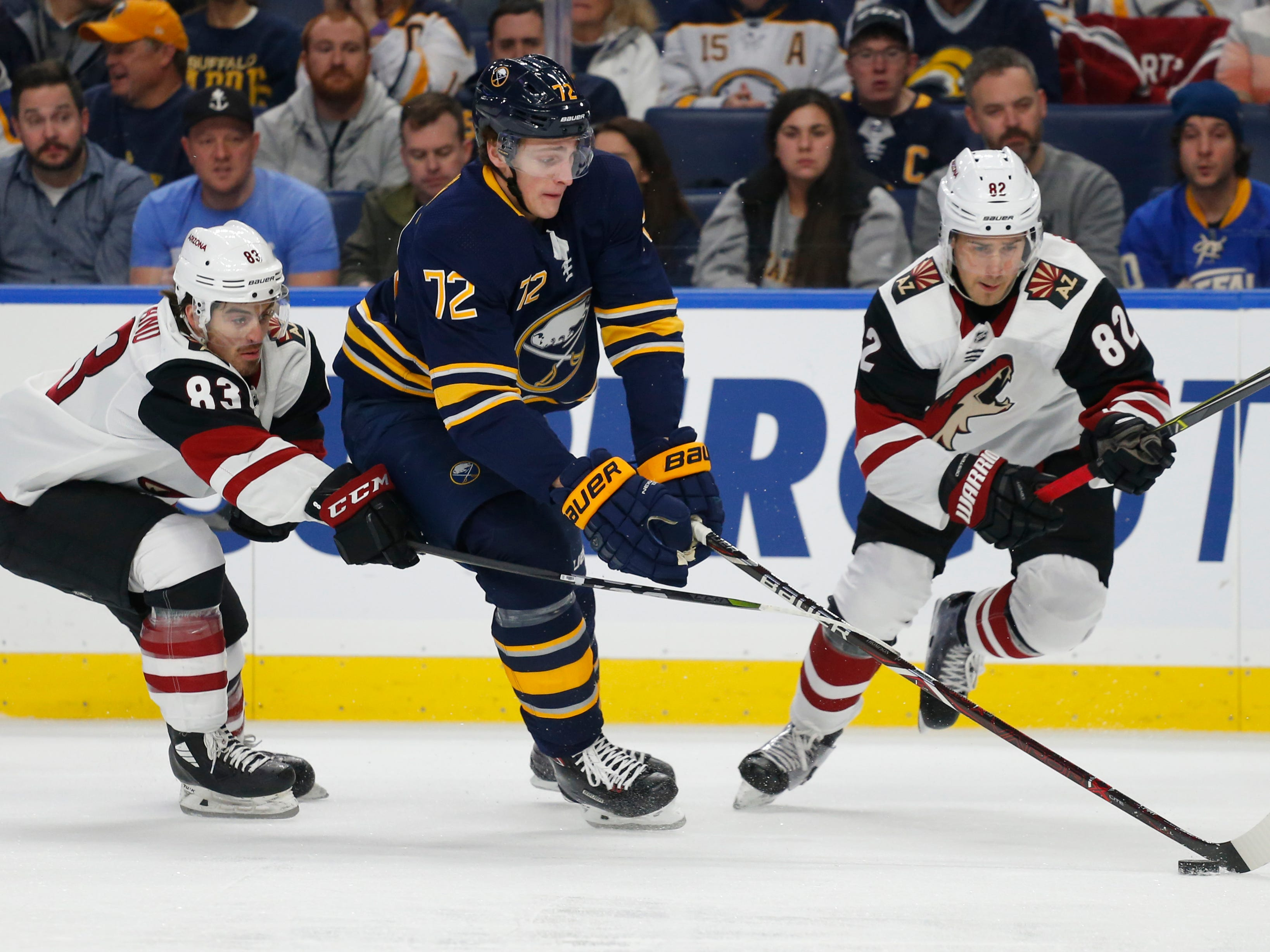 Buffalo Sabres forward Tage Thompson (72) carries the puck between Arizona Coyotes Conor Garland (83) and Jordan Oesterle (82) during the first period of an NHL hockey game, Thursday, Dec. 13, 2018, in Buffalo N.Y. (AP Photo/Jeffrey T. Barnes)