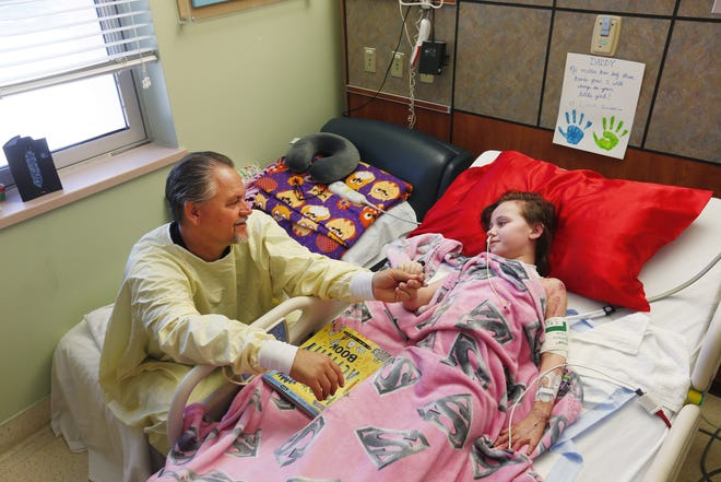 J.D. McCune sits bedside with his daughter, Isabella, at the Arizona Burn Center in Phoenix June 17, 2018. She was severely burned in a home accident in March.