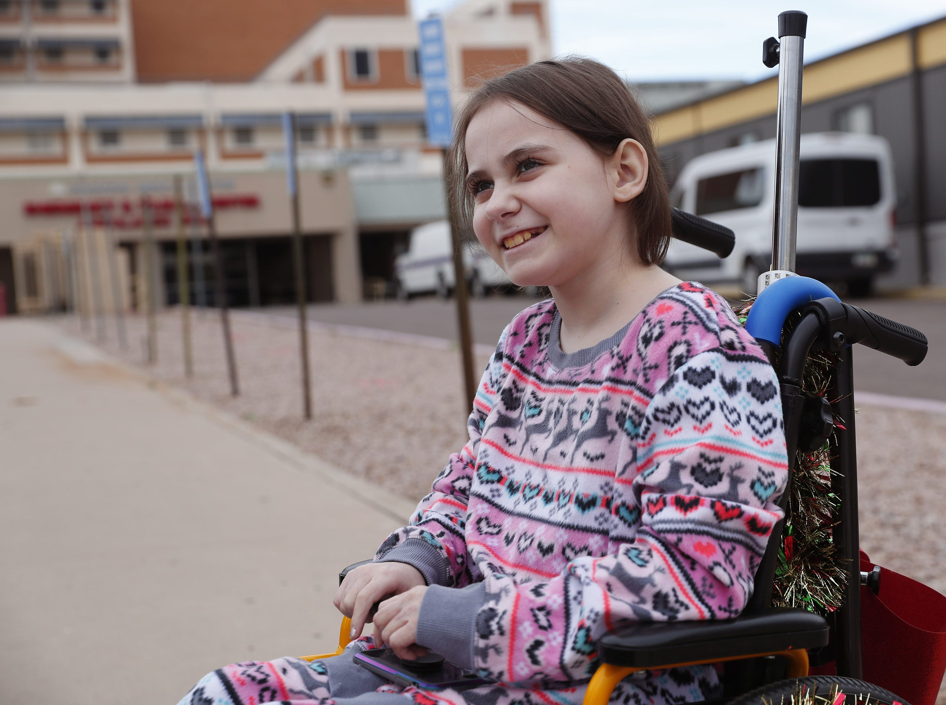 Isabella McCune sits in her wheelchair outside the Arizona Burn Center in Phoenix Dec. 12, 2018. The 9-year-old was severely burned in a home accident in March.