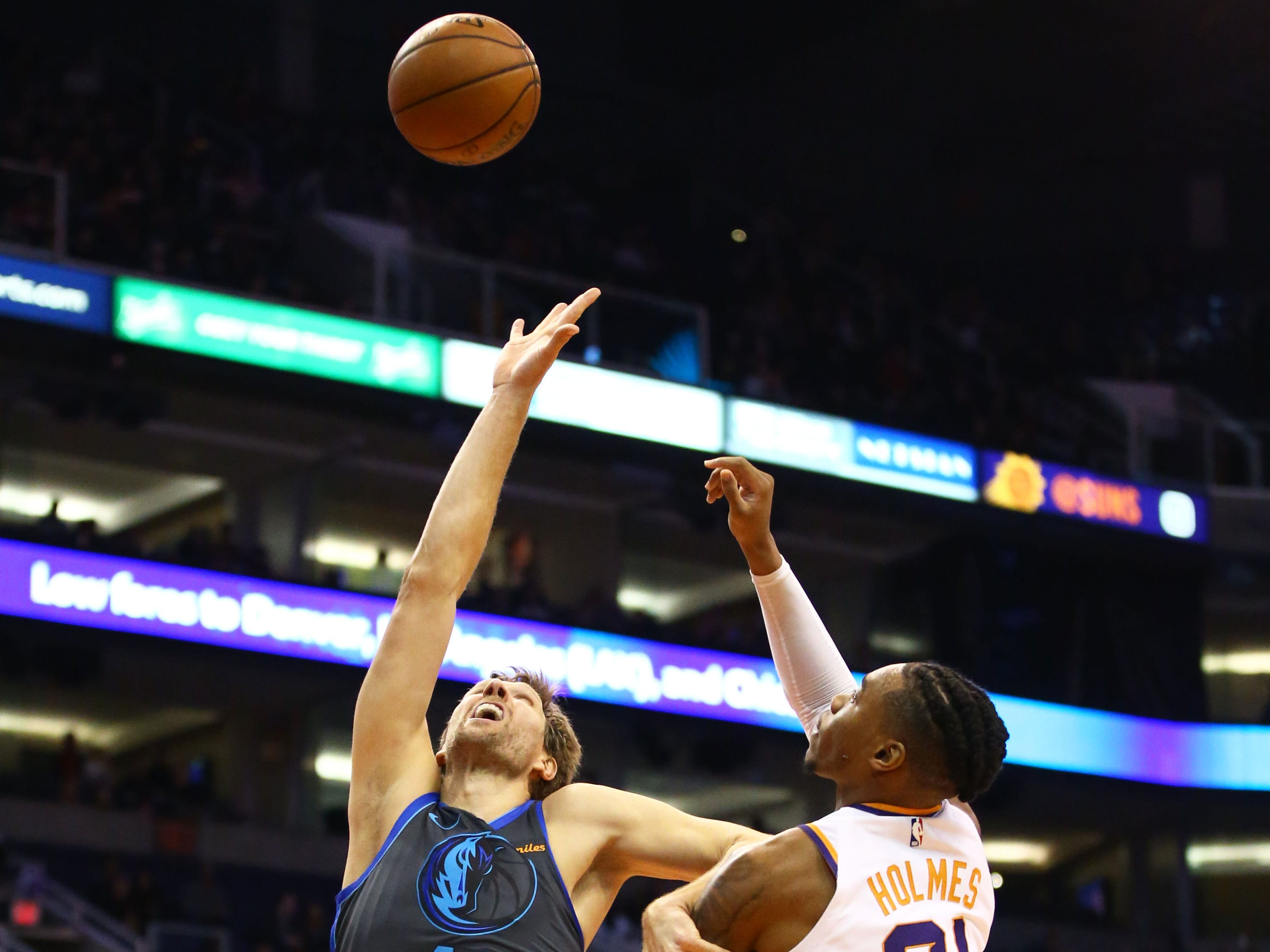 Phoenix Suns forward Richaun Holmes battles for the rebound with Dallas Mavericks' Dirk Nowitzki during a game on Dec. 13 at Talking Stick Resort Arena.