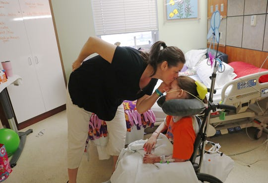 Lilly McCune kisses her daughter, Isabella, as she recovers in her room at the Arizona Burn Center in Phoenix June 14, 2018. She was severely burned in a home accident in March.