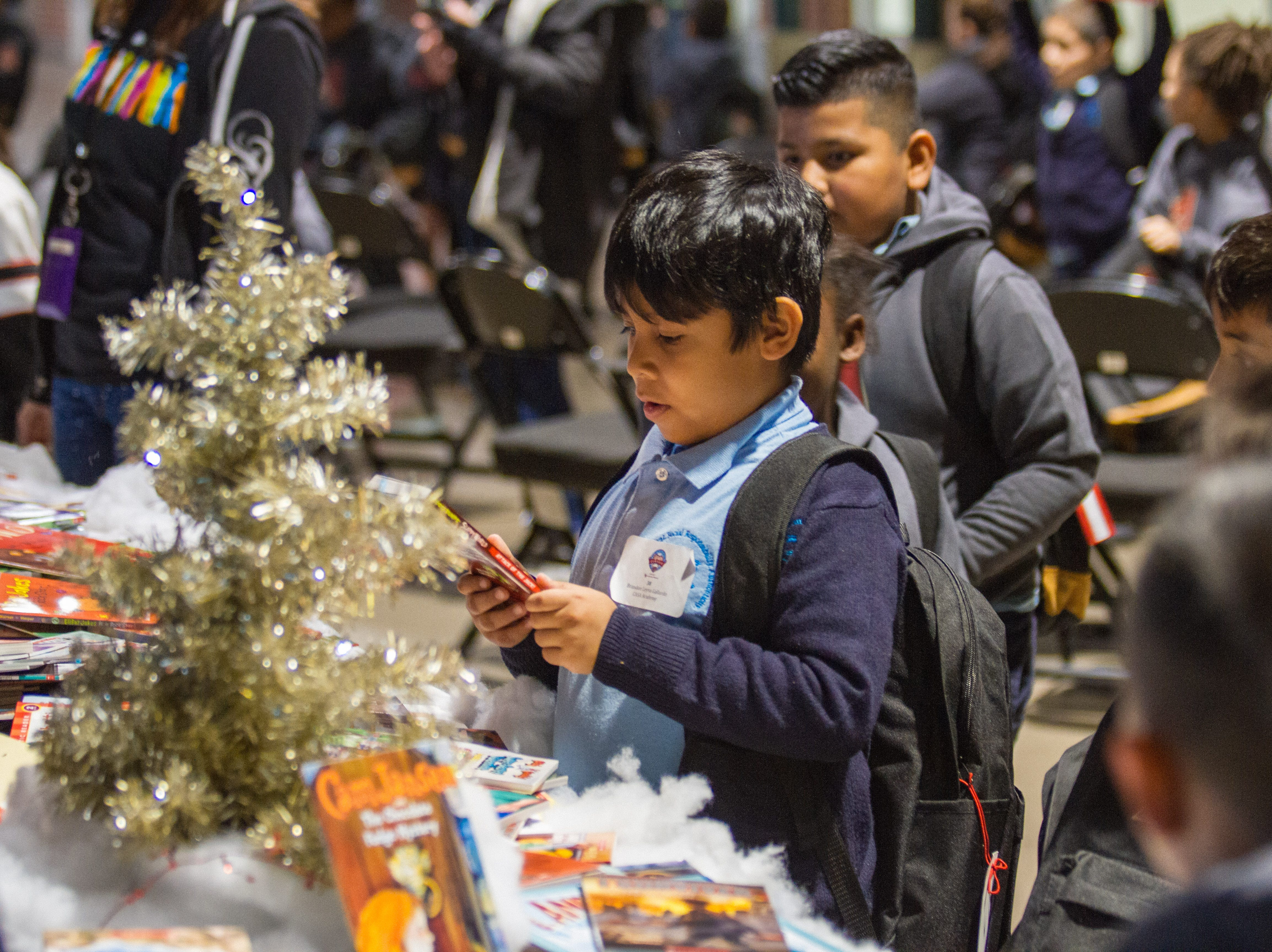 Children pick up coloring supplies  during the Arizona Diamondbacks annual Winter Classic Holiday Party inside Chase Field in Phoenix, Arizona on Friday, Dec. 14, 2018.