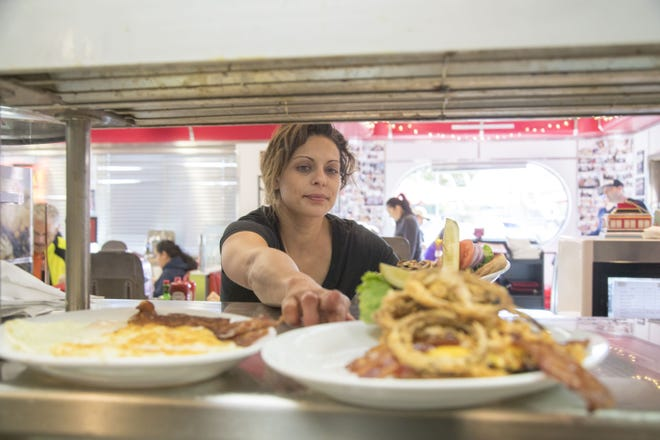 A waitress retrieves dishes at Chase's Diner in Chandler. If restaurants and bars are considered a non-taxable service under a new Arizona law, city budgets could take a big hit.