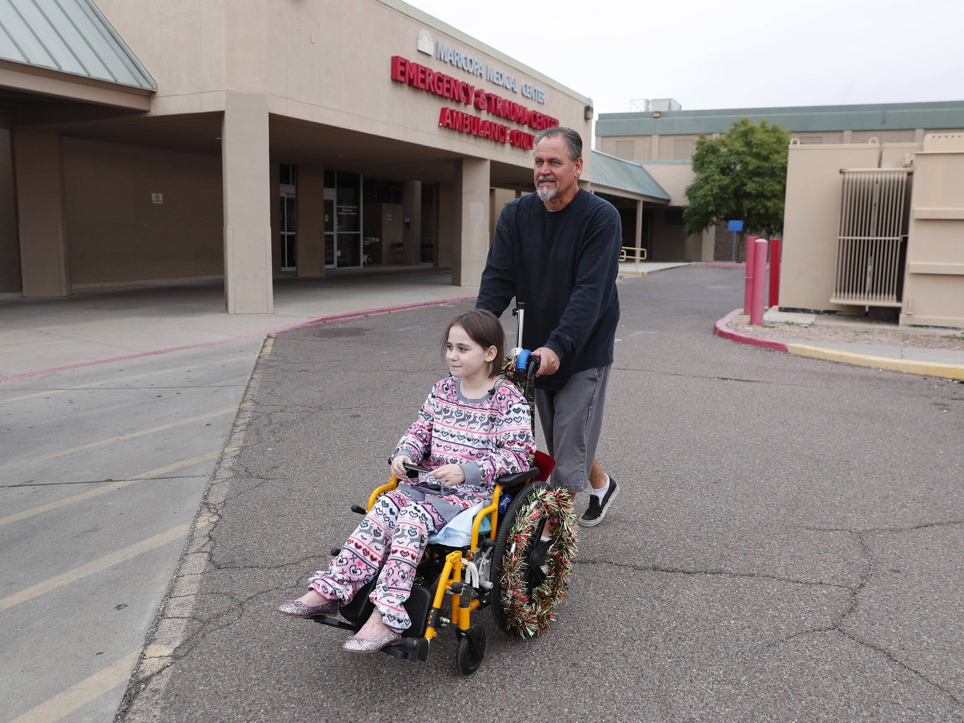 Isabella McCune is pushed in her wheelchair by her dad, J.D., at the Arizona Burn Center in Phoenix Dec. 12, 2018. The 9-year-old was severely burned in a home accident in March.