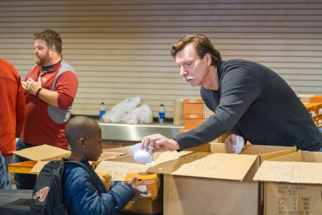 Legendary Hall of Famer, Randy Johnson, hands out socks after children receive shoes during the Arizona Diamondbacks annual Winter Classic Holiday Party inside Chase Field in Phoenix, Arizona on Friday, Dec. 14, 2018.