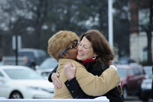 Port Huron Councilwoman Anita Ashford hugs sculptor Mino Duffy Kramer during the unveiling of a statue Friday, Dec. 14, honoring William Pitt Edison.