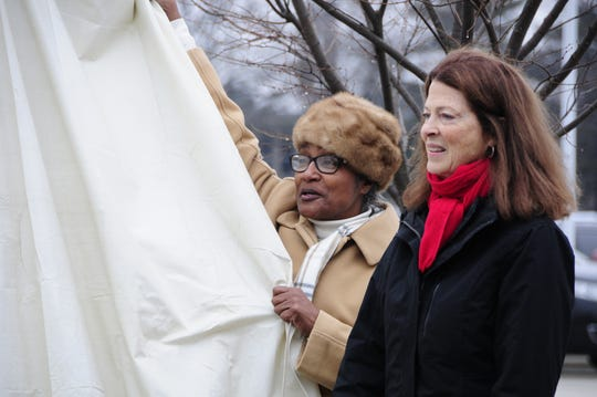 Port Huron Councilwoman Anita Ashford and sculptor Mino Duffy Kramer unveil a statue Friday, Dec. 14, 2018 honoring William Pitt Edison.