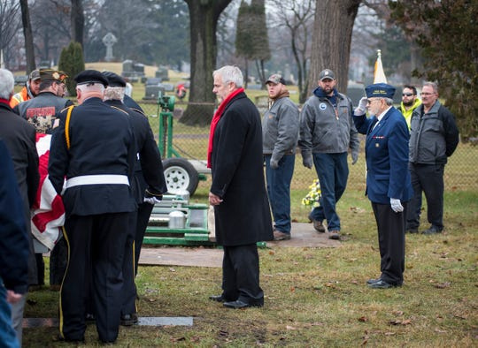 St. Clair County Allied Veterans Council member Dave Norris, right, holds a salute as pallbearers carry the casket of Joseph A. Humphries to his gravesite Friday, Dec. 14, 2018 at the Allied Veterans Cemetery in Fort Gratiot.