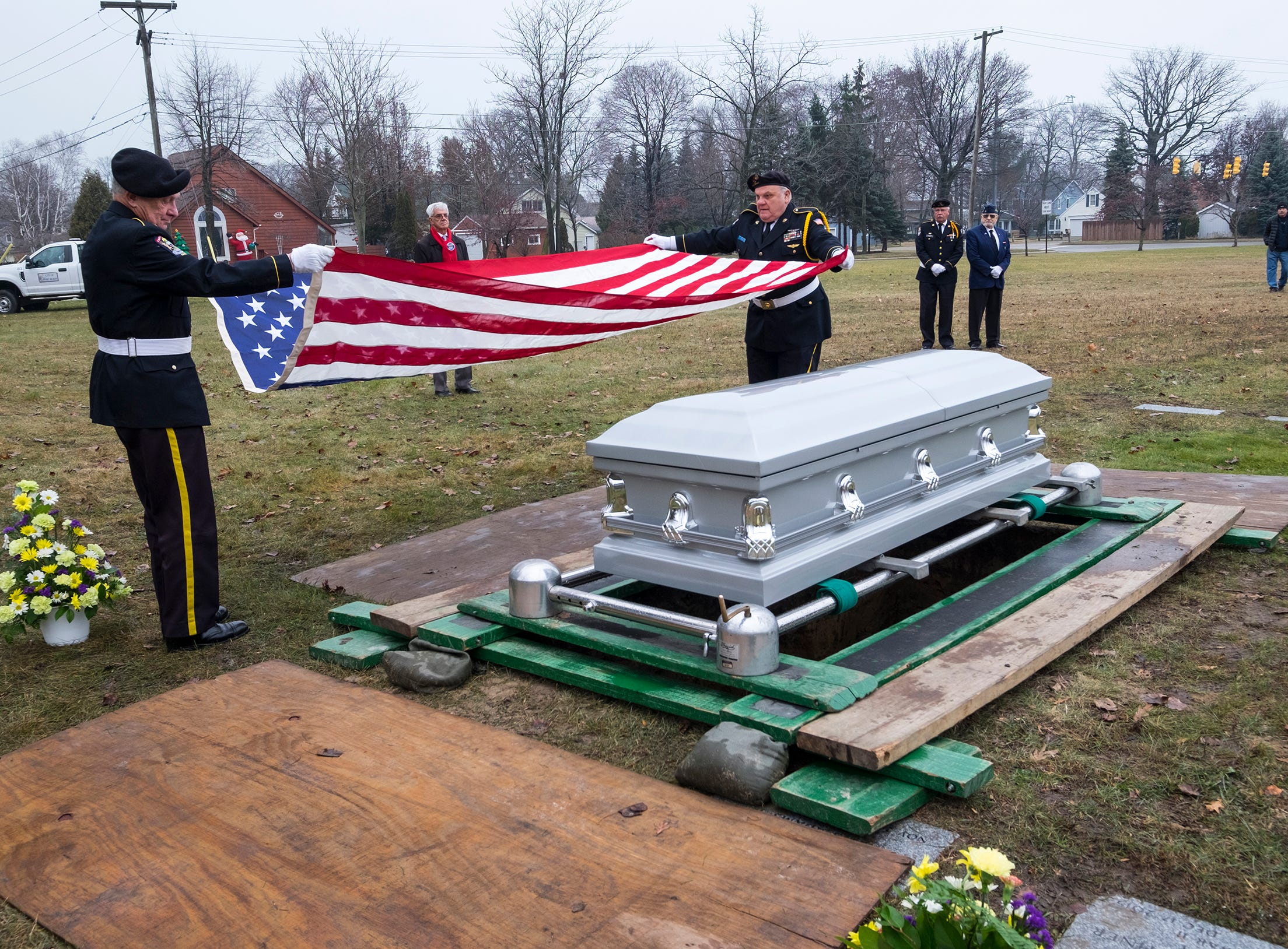 St. Clair County Allied Veterans Council members Bill Livesay, left, and Dave Robinson fold an American flag that was draped over  the casket of Joseph A. Humphries during his funeral Friday, Dec. 14, 2018 at Allied Veterans Cemetery in Fort Gratiot.