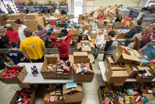 Students and faculty from Woodland Development Center in Marysville pack Salvation Army food boxes Friday, Dec. 14, 2018 at a warehouse in Port Huron.  A Salvation Army food box makes its way down an assembly line while students and faculty from Woodland Development Center in Marysville pack it with nonperishable food items Friday, Dec. 14, 2018 at a warehouse in Port Huron.