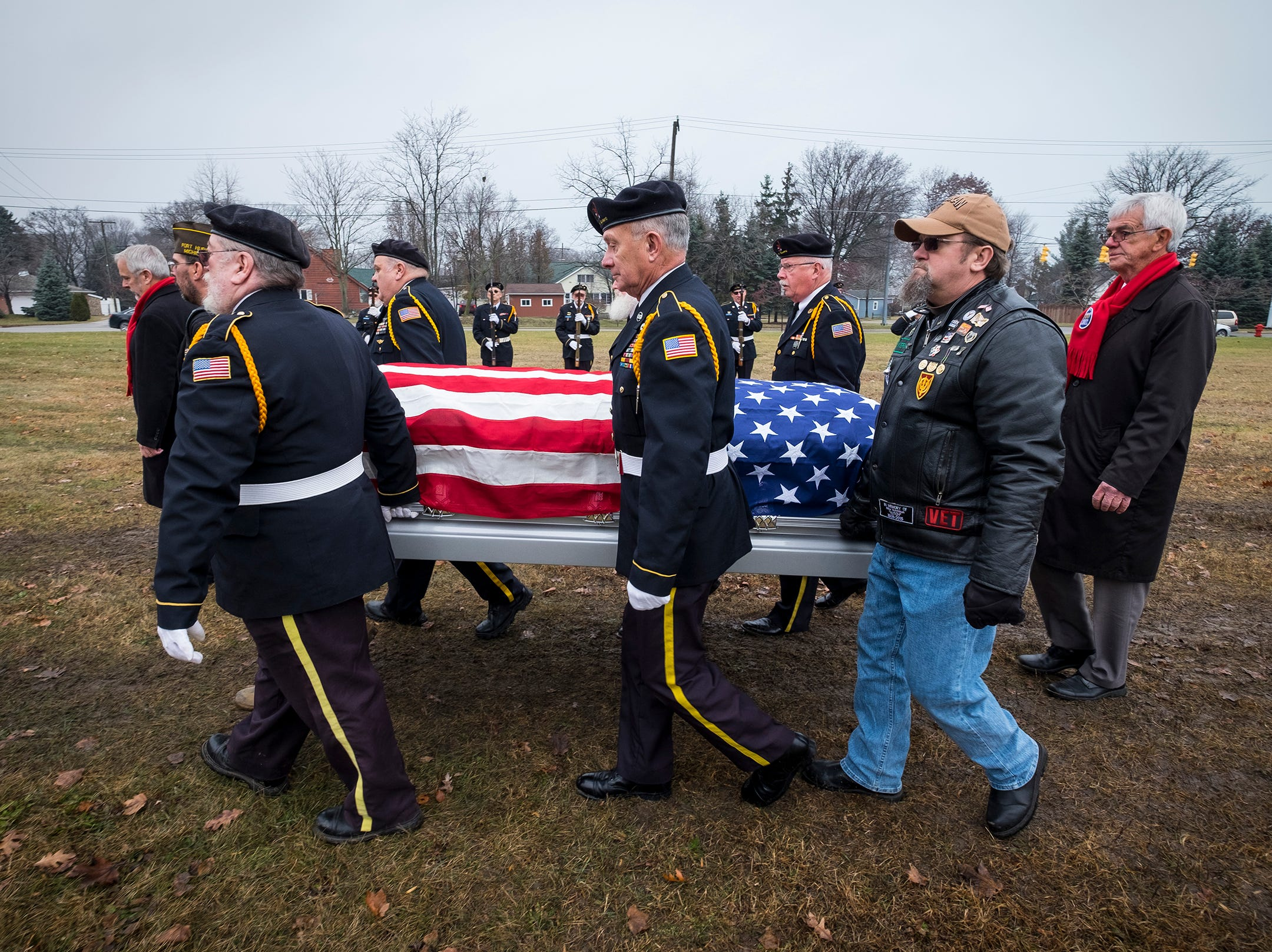 The casket of Joseph A. Humphries is carried past members of the St. Clair County Allied Veterans Council Honor Guard at the start of his funeral service Friday, Dec. 14, 2018 at the Allied Veterans Cemetery in Fort Gratiot.