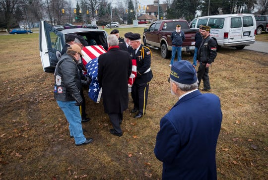St. Clair County Allied Veterans Council member  Dave Norris, right,  watches as pallbearers remove the casket of Joseph A. Humphries from the back of a hearse Friday, Dec. 14, 2018 at the Allied Veterans Cemetery.