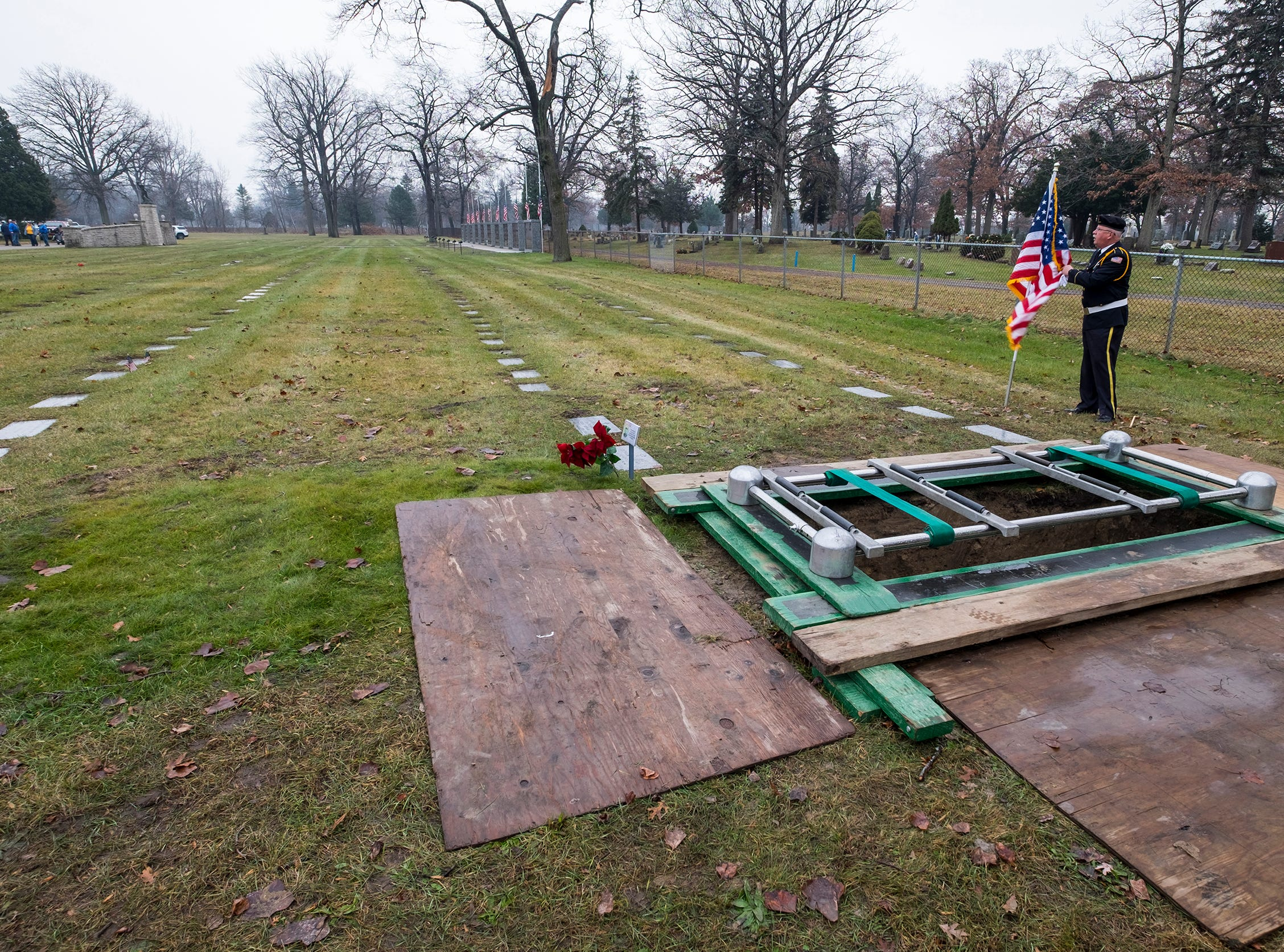 St. Clair County Allied Veterans Council Honor Guard member Lee Pochert sets an American flag next to the gravesite for Joseph A. Humphries Friday, Dec. 14, 2018 at the Allied Veterans Cemetery in Fort Gratiot.