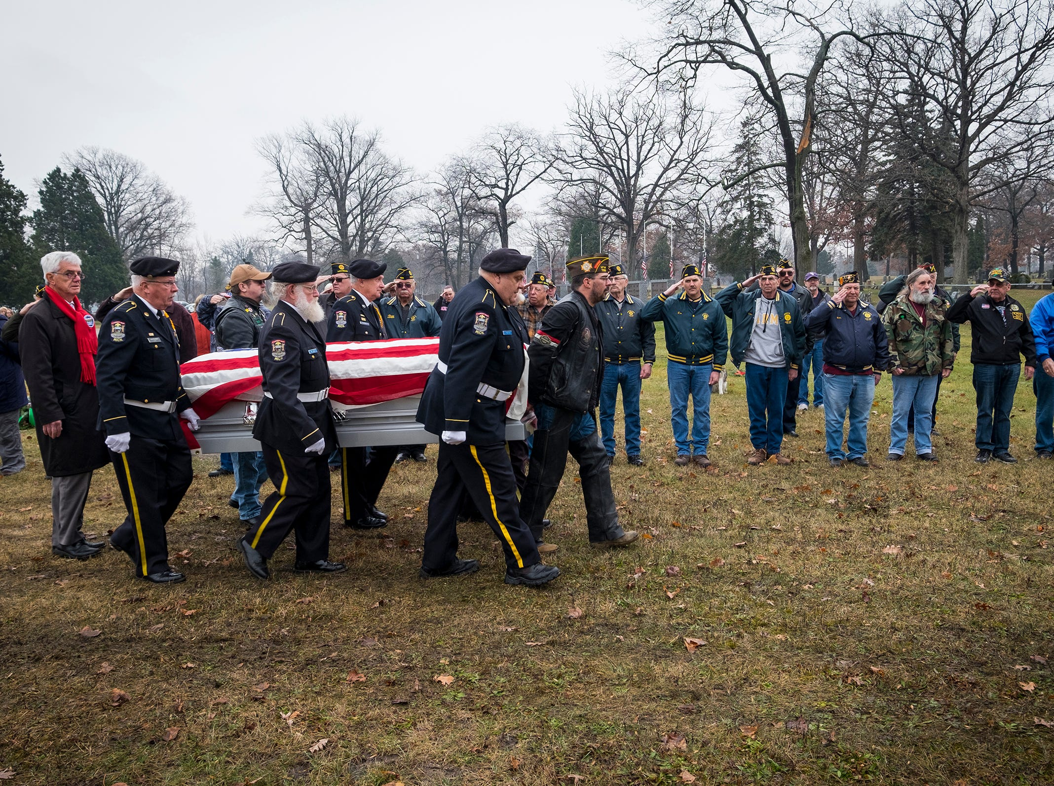 Veterans in attendance hold a salute while the casket of Joseph A. Humphries is carried to his gravesite Friday, Dec. 14, 2018. Humphries, a U.S. Army veteran, was born and lived in Port Huron but has no known relatives in the area.