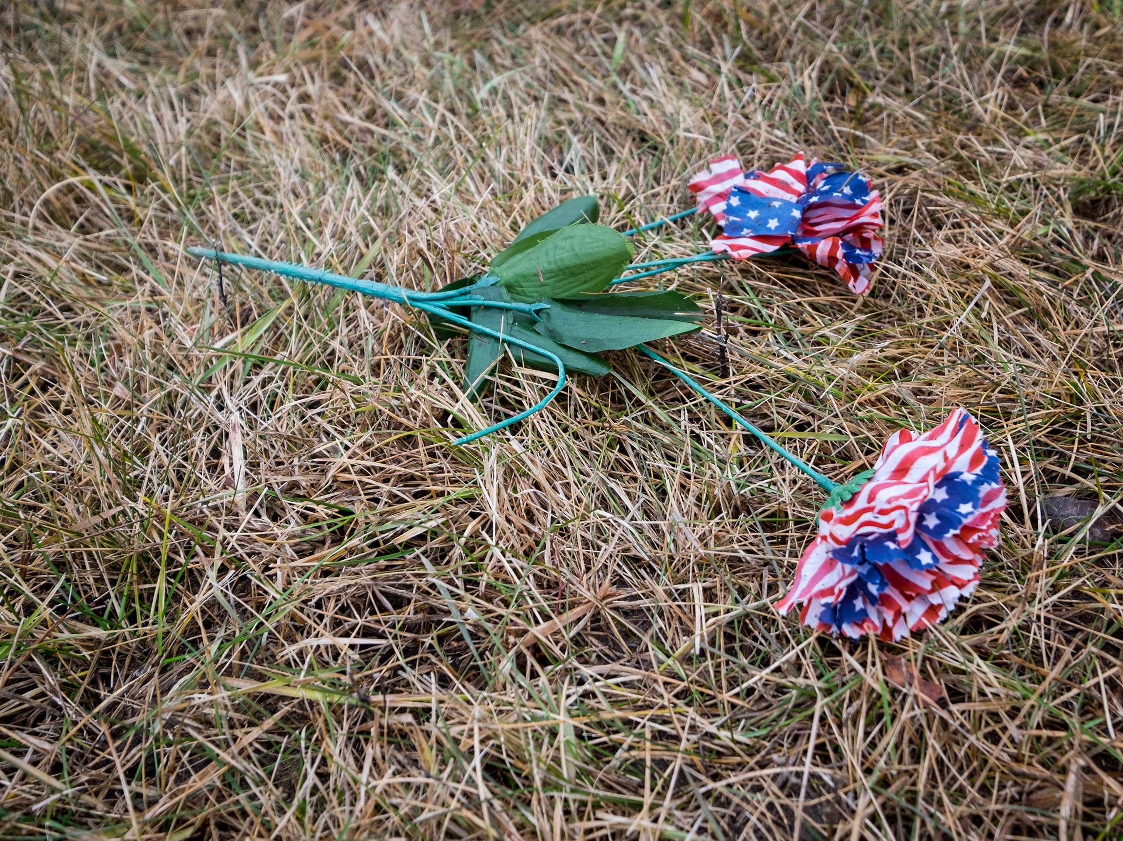 A flower made out of American flag tissue paper sits in the grass at the Allied Veterans Cemetary Friday, Dec. 14, 2018 before the funeral for Joseph A. Humphries.