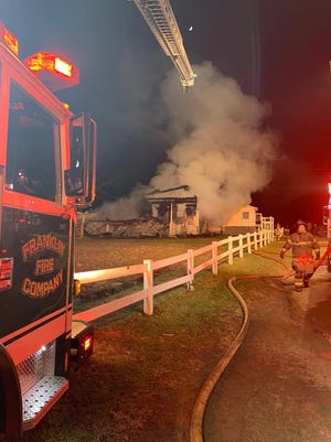 Franklin Fire Company's ladder truck sets up at a house fire on a dirt lane off Creek Road, Metal Township, on Thursday, Dec. 13, 2018.