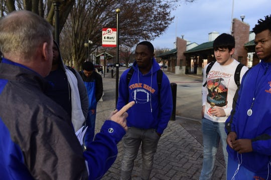 York High football assistant coach Mike Teyral, left, checks in with players at the bus transfer station in York before the players leave the station for Ballyhoo Sports Academy at Heritage Hills Thursday, Dec. 13, 2018.