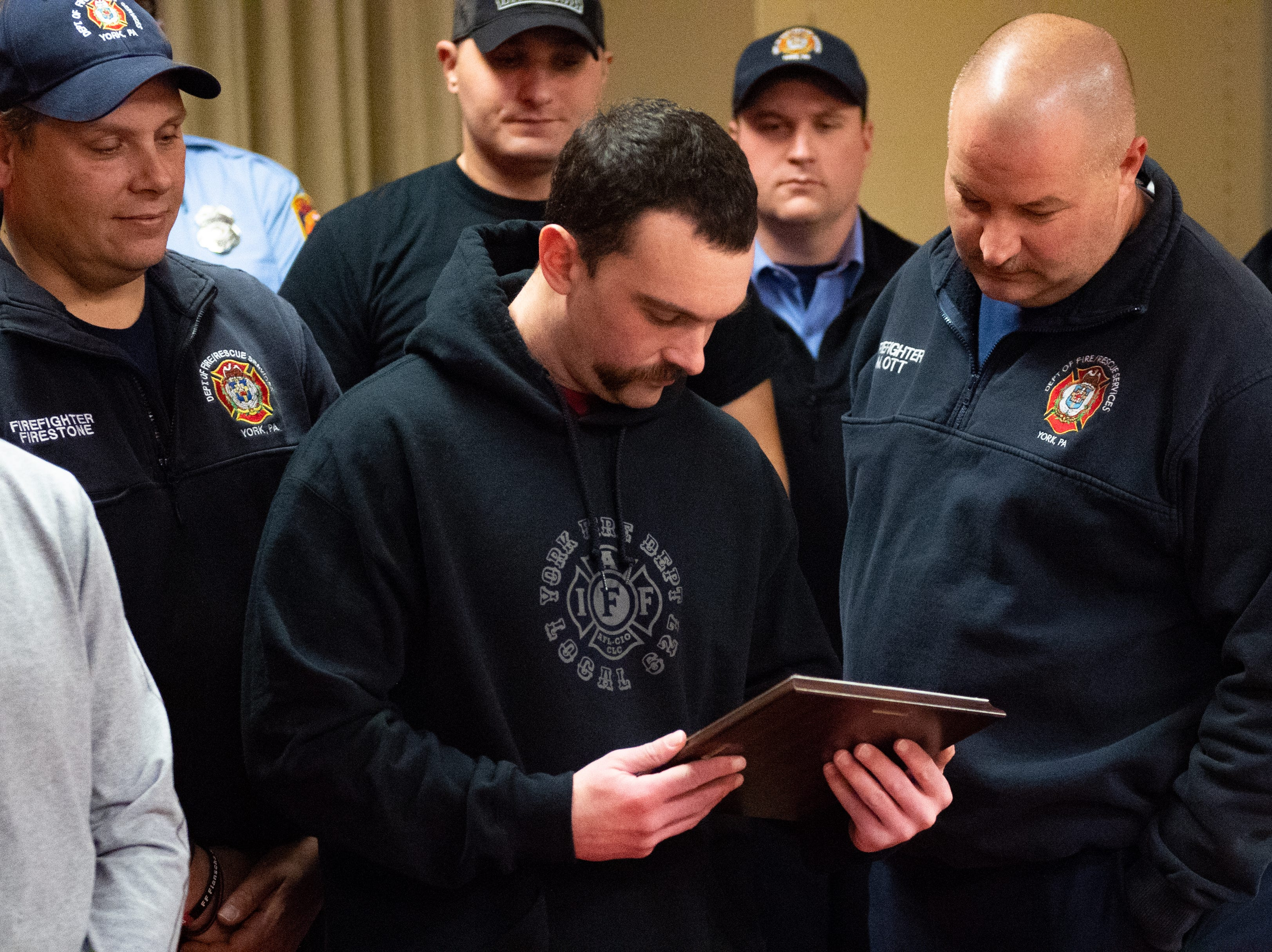 The firefighters passed the plaque around taking time to fully take in the pictures instilled on the wood, December 13, 2018.
