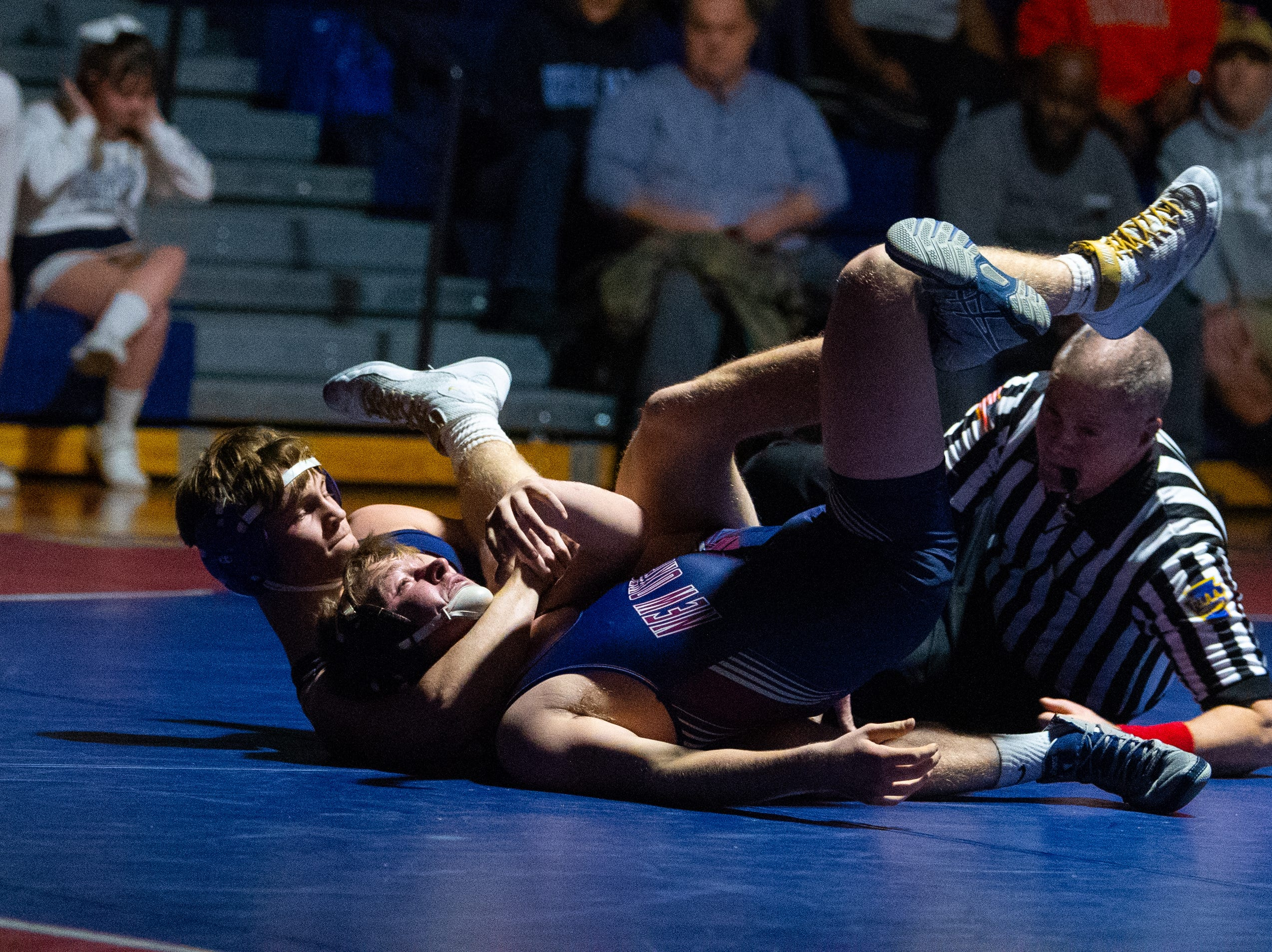 Dallastown's John Ligon locks up Kinser Laughman of New Oxford during the YAIAA Division I wrestling match, December 13, 2018. The Wildcats defeated the Colonials 40-20.