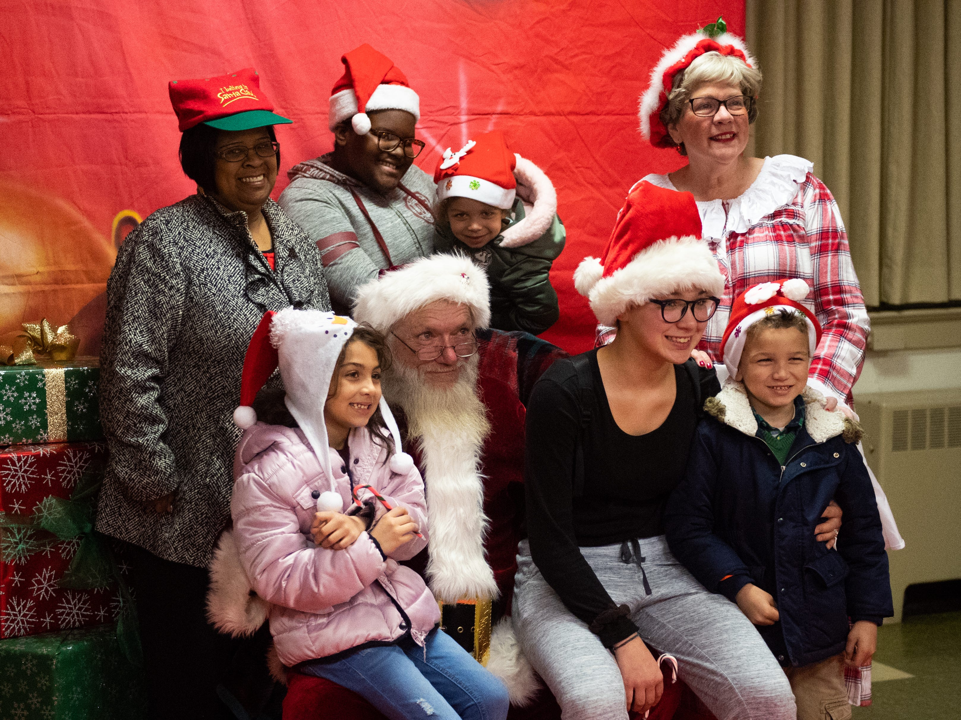 (left to right, top to bottom) Shirley Towles, TaJayla Williams, Kaylona Gadlin, Asi'lynn Gadlin, Rae'yhona Gadlin and Kay'lon Gadlin huddle together for a picture with Santa and Mrs. Claus during the Annual Evening with Santa, December 13, 2018.