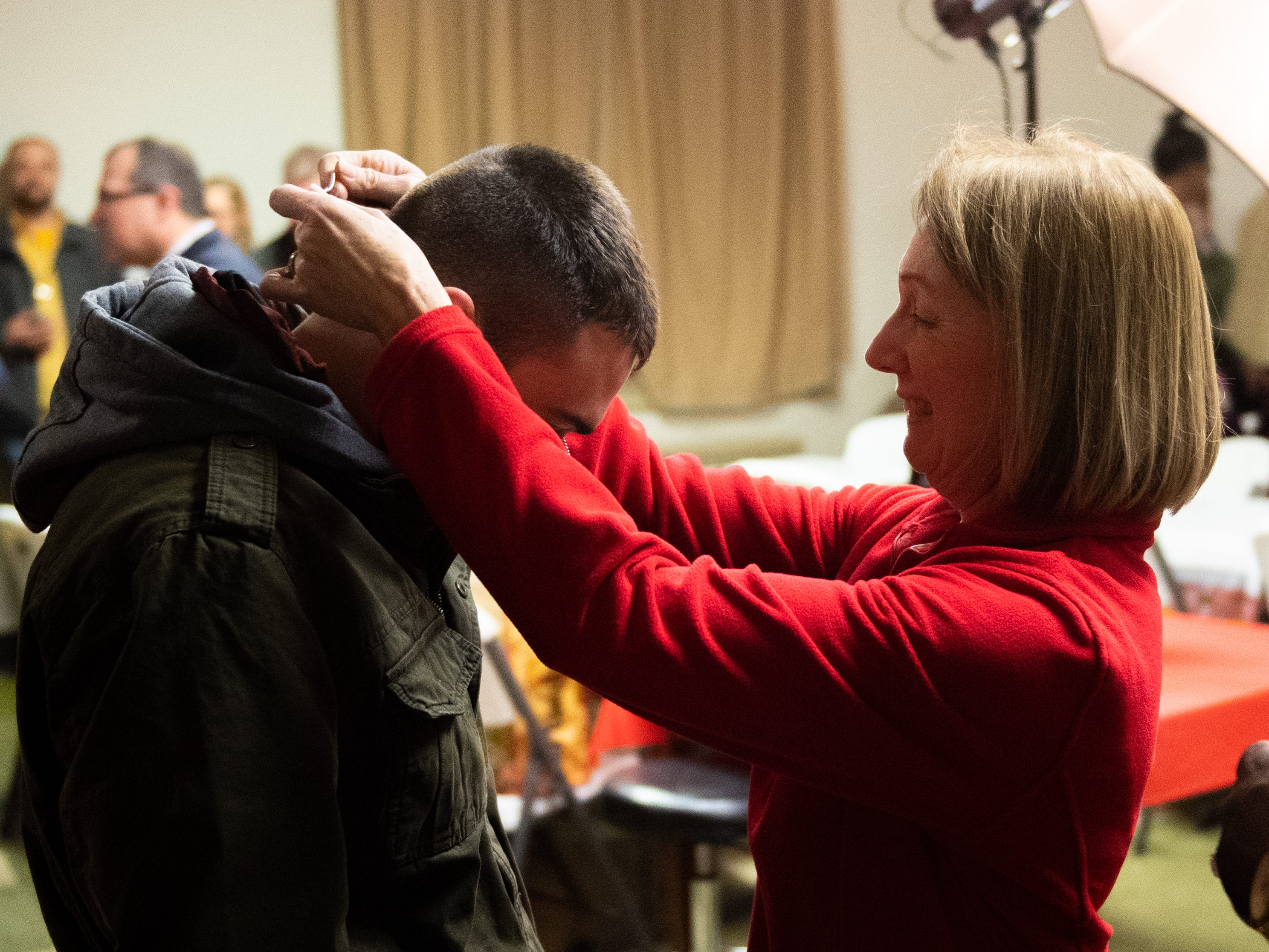 Beth Beecher places dog tags around a firefighter's neck, December 13, 2018.