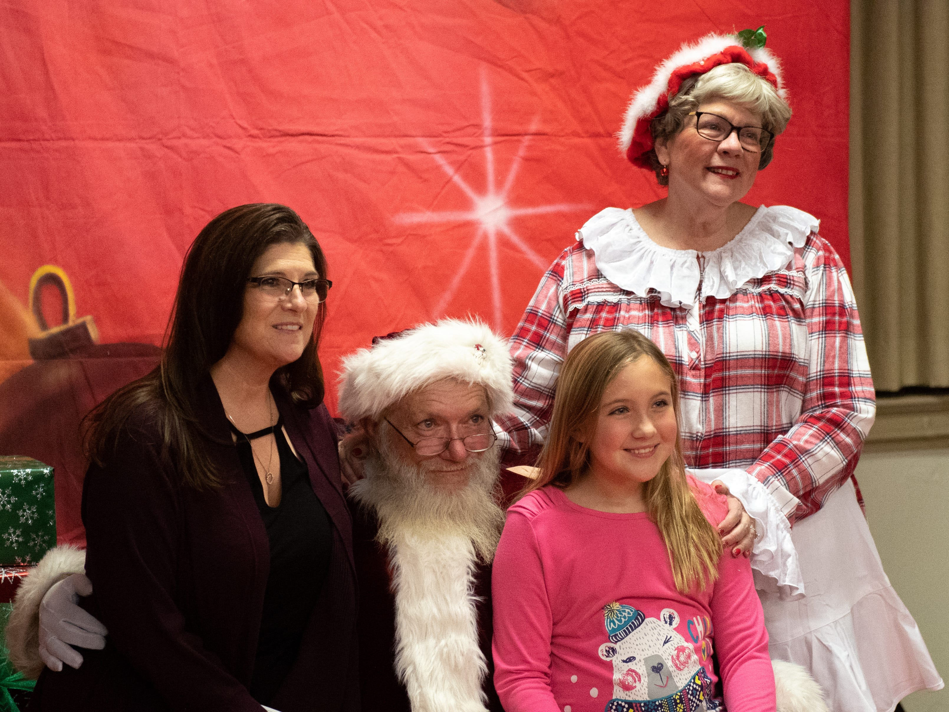 Nancy Fuentes (left) and her daughter, Rio (right), pose with Santa and Mrs. Claus during the Annual Evening with Santa at the Lincoln Engine Company, December 13, 2018.