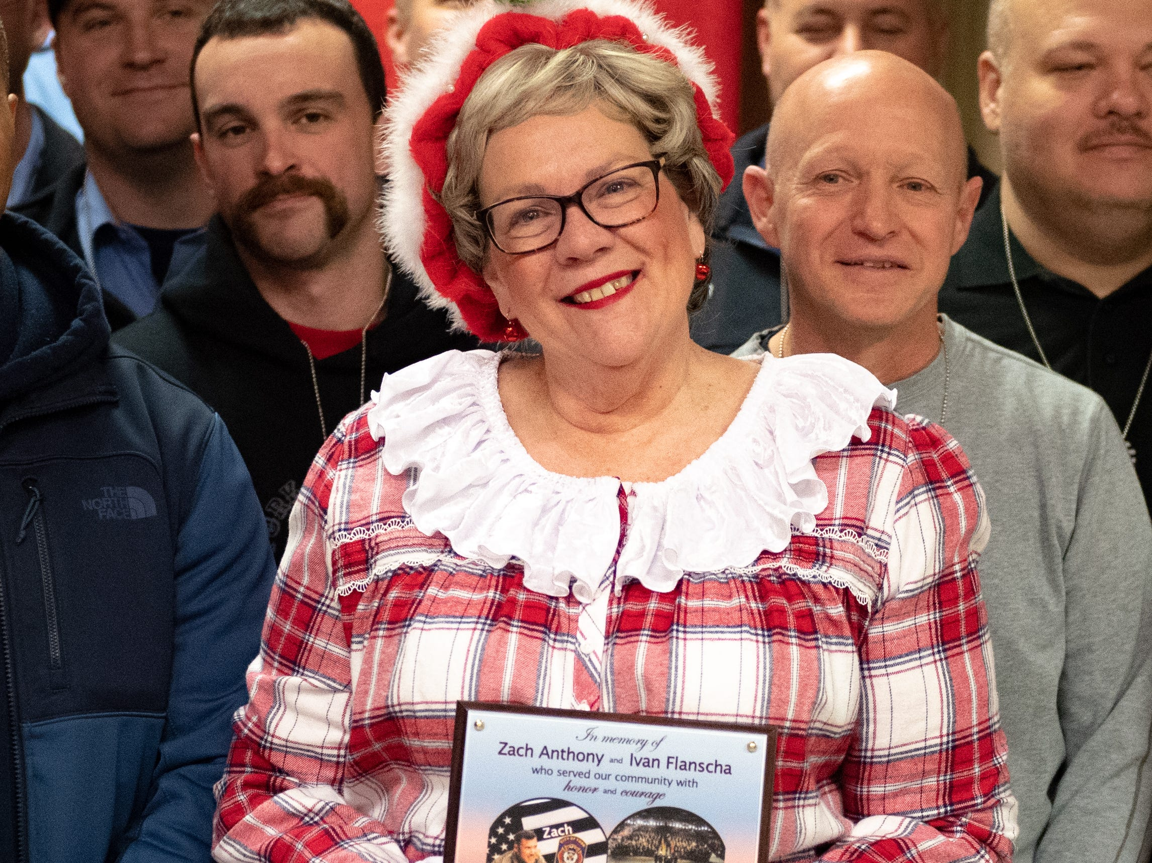 Mrs. Claus stands front and center holding the plaque, December 13, 2018.