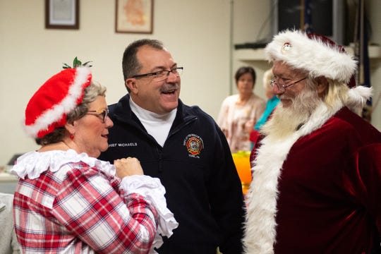 After all of the firefighters were honored, Fire Chief Dave Michaels talked with Mr. and Mrs. Claus before the children arrive for Evening with Santa, December 13, 2018.