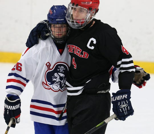 Fairport's Nick Krug, and Penfield's  Jack Schlifke hug after the Red Raiders and Patriots played to a 2-2 tie in December. Schlifke and Krug are both players to keep an eye on during the Section V Class A Tournament.