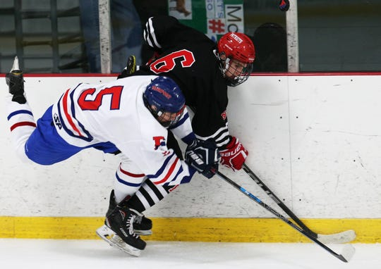 Fairport's Sam Hoyen battles Penfield's Cole Patton along the boards during Thursday night's 2-2 tie at the Rochester Ice Center.