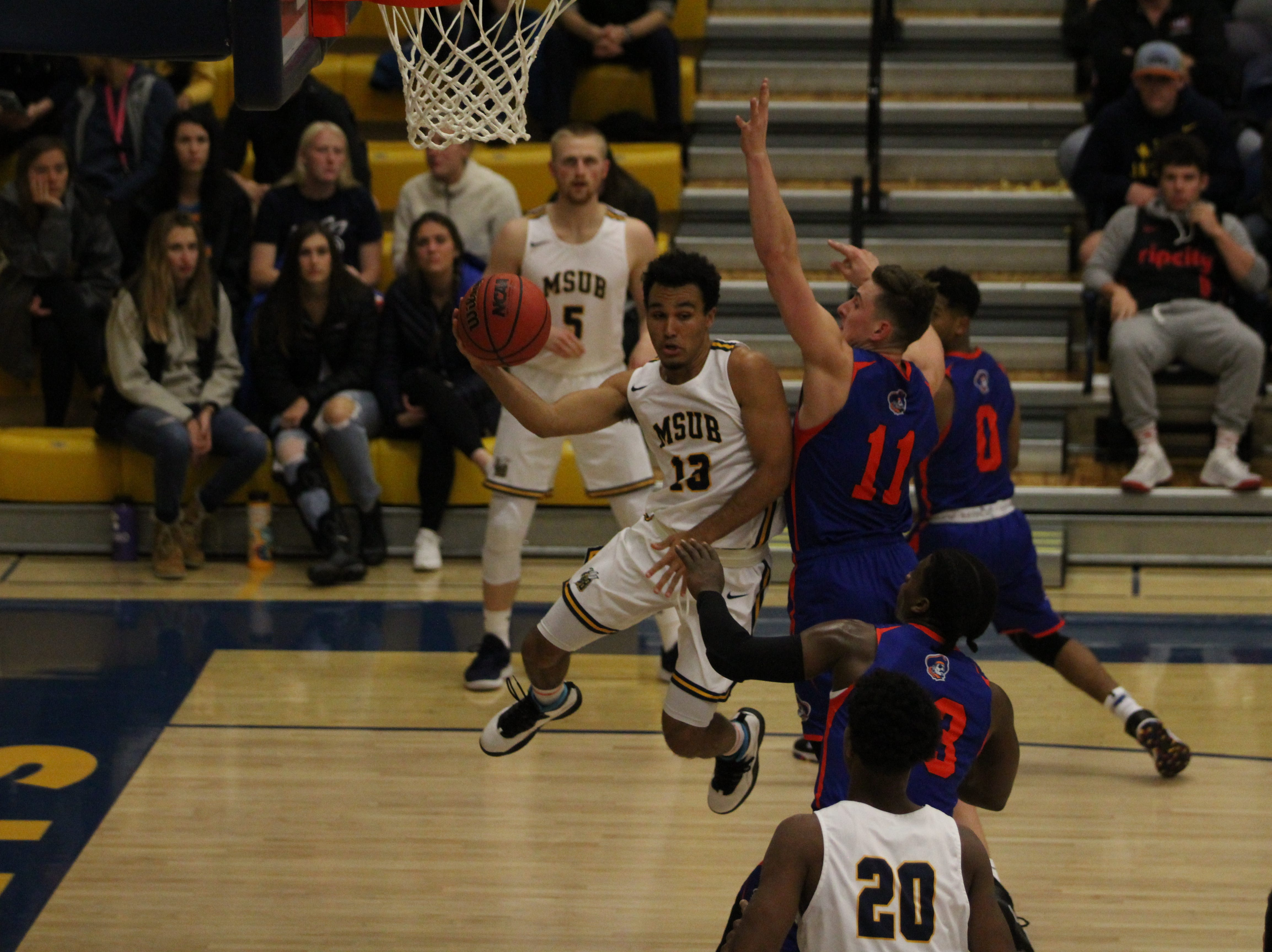 Tyler Green attempts to pass the ball from under the rim.