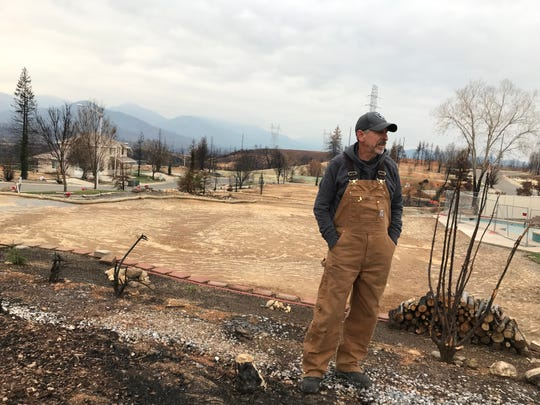 The scene in December: Dan Kissick takes a break from cutting down burned trees on the property. He and his wife are rebuilding.