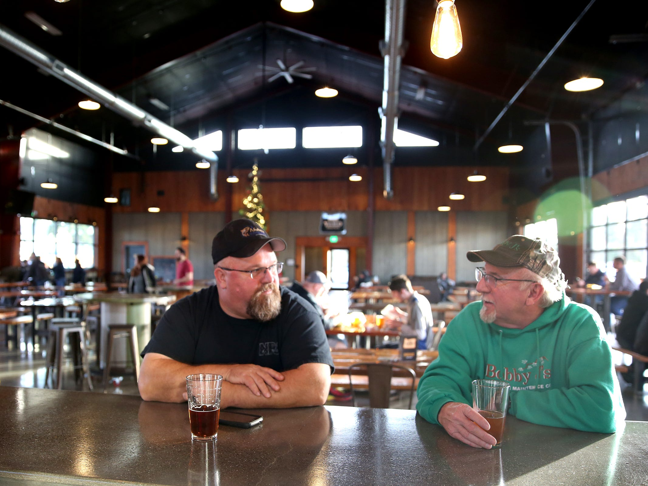 Salem residents Eric White and Bob Johnson enjoy a beer on opening day of The Yard Food Park in Salem on Thursday, Dec. 13, 2018.