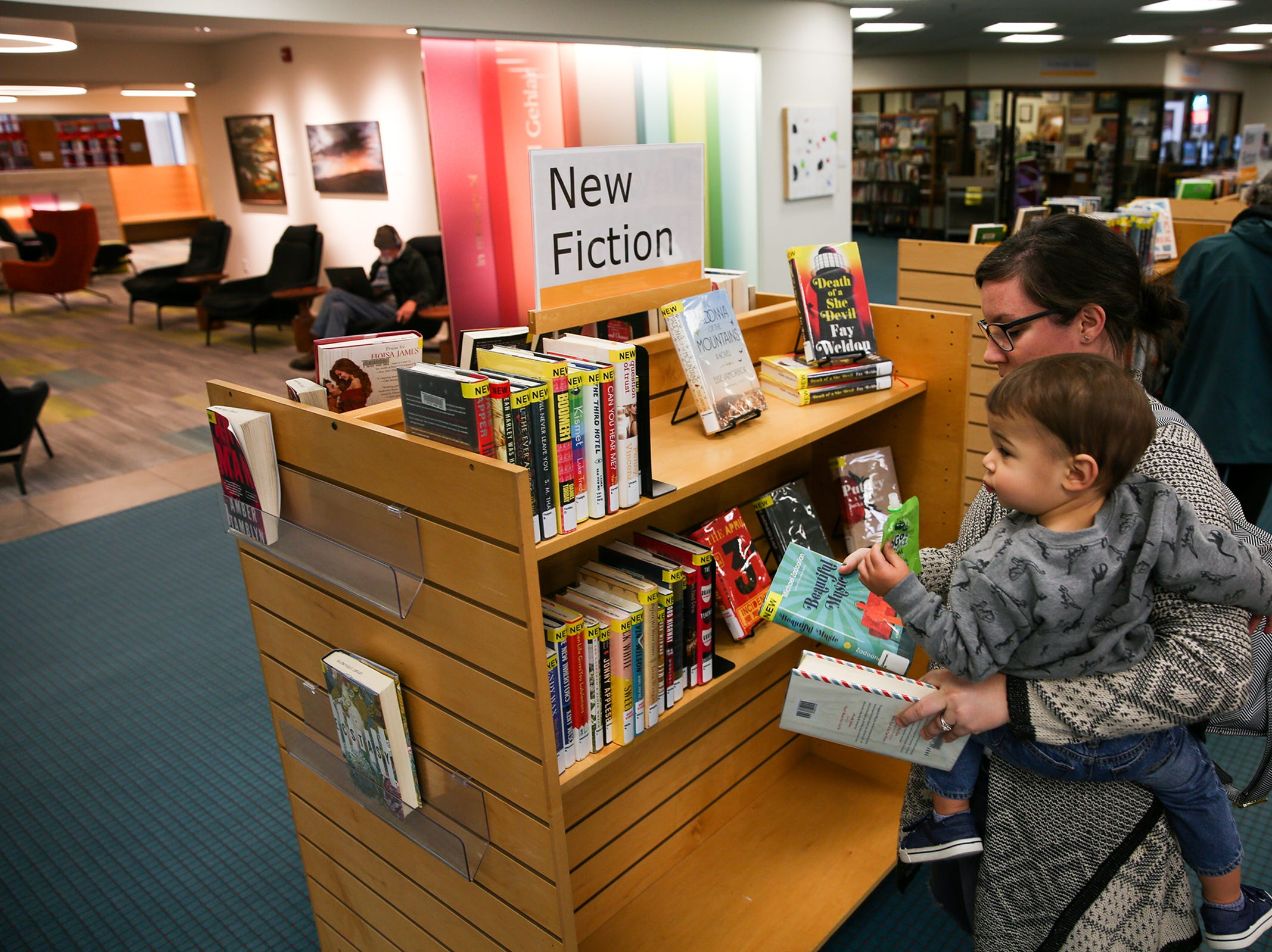 Lindsay DiPasquale and her one-year-old son look through newly released books at the Salem Public Library on Friday, Dec. 14, 2018.