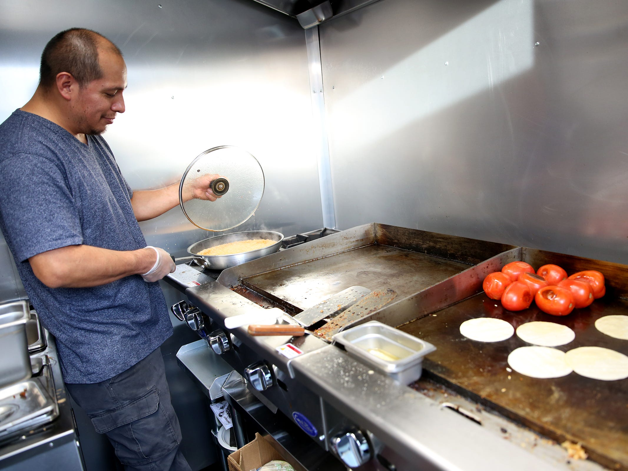 Owner of Paco's Mexican Food, Israel Garcia, prepares al pastor tacos in his food truck on opening day of The Yard Food Park in Salem on Thursday, Dec. 13, 2018.