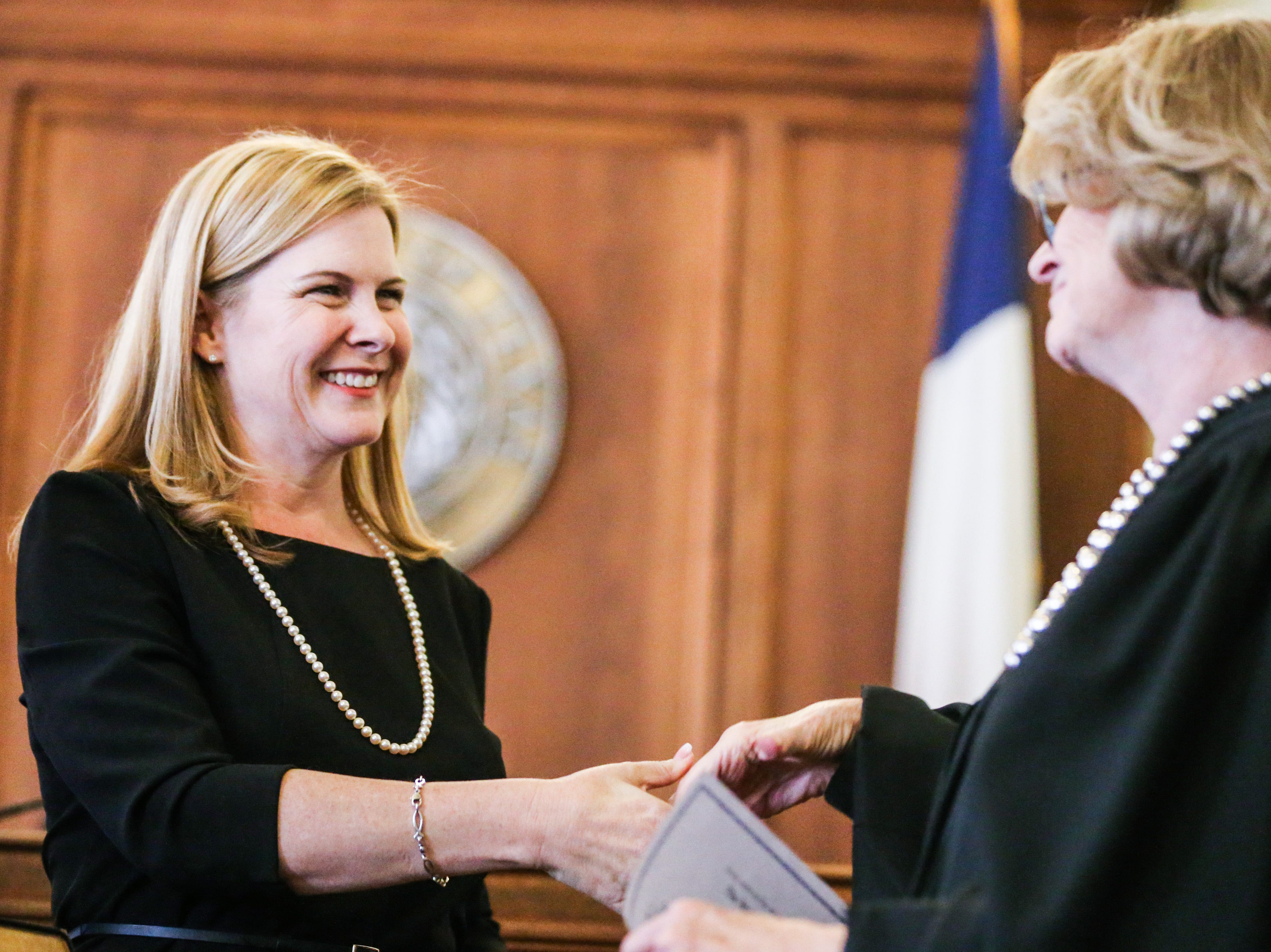 Carmen Dusek shakes hands with Justice Barbara Walther after she is sworn in as 51st District Court judge Friday, Dec. 14, 2018, at Tom Green Courthouse.