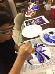 Students paint during a Chinese Mask Class at Concho Arts and Crafts, at 209 S. Magdalen St.